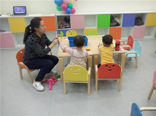 乐高教室里,小朋友们与老师一起学用乐高积木拼成